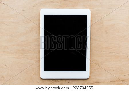 top view of one turned off tablet on wooden table