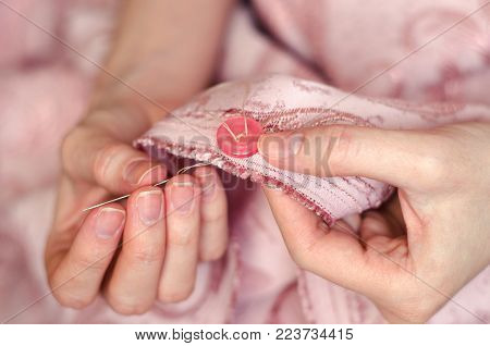 Hands of a young girl sew a button with a needle close up