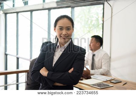 asian businesswoman smiling at camera while colleagues have meeting at office. businessman working with co worker team at workplace