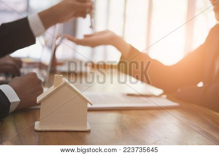 real estate agent have a meeting with customer. sale & purchase property with house model, key and signing contract document. realtor talk with client.