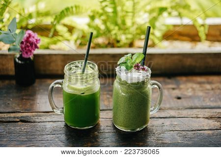 two green smoothie smoothies with a spirulina and spinach on a wooden table in the loft style. Tropical healthy drinks.