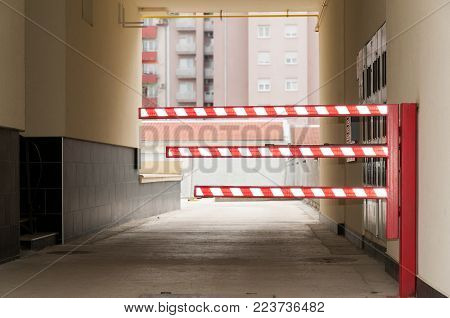 Traffic car barrier with red and white fluorescent reflective light on the entrance of private building parking lot where only tenants can park vehicles