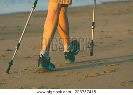 Legs and poles of nordic walker old woman on the beach.