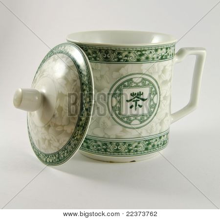 Chinese mug with a cap leaning on it.