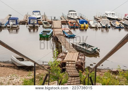 Small wooden pedestrian bridge and parking lot small boats and motorboats on the river Volga in rainy summer day.