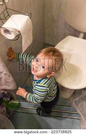 Little Boy Staying Next To The Toilet And Toilet Paper