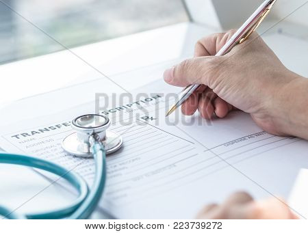 Doctor Writing On Medical Health Care Record, Patients Discharge, Or Prescription Form Paperwork In