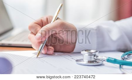 Doctor writing on medical health care record, patients discharge, or prescription form paperwork in hospital clinic office with physician's stethoscope on desk