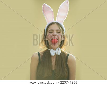 Easter Girl Holding Red Egg In Mouth On Beige Background. Woman With Rosy Bunny Ears And Bow. Fertil