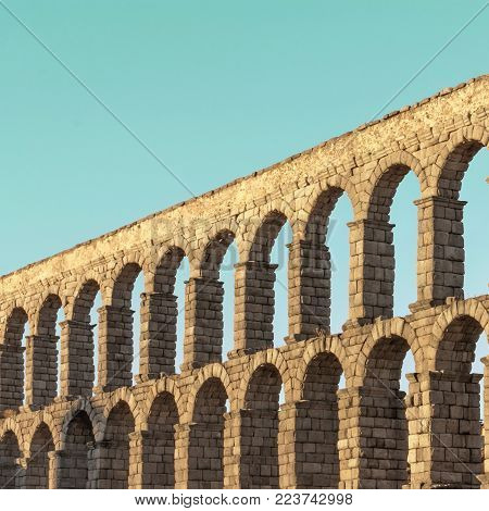 A square photo of an ancient Roman aqueduct in Segovia, Spain
