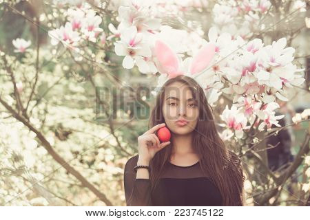 easter egg in hand of woman or adorable girl with sexy, plush lips and rosy bunny ears on long, brunette hair at blossoming, magnolia flowers, trees, garden on floral background. Easter. Spring