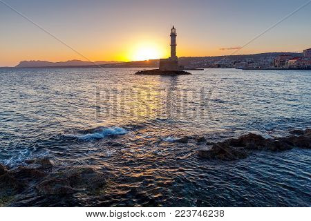 Old stone lighthouse in the Venetian harbor at dawn. Chania. Crete.