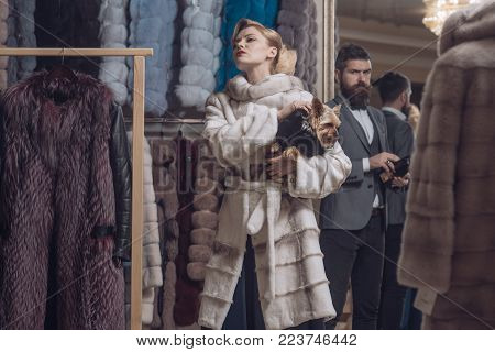 Date, couple, love, man and woman. Fashion and beauty, winter. Woman in fur coat with man, shopping, seller and customer. Couple in love among fur coat with dog, luxury. Purchase, business, moneybags.