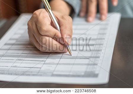 Administrator's hand fill in business schedule form document writing on yearly work plan, monthly timetable sheet, or weekly time table paper for office tasks, things and jobs to do list