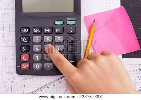 Scientific Calculator In The Action Hands During Mathematical Lesson. School Concept.