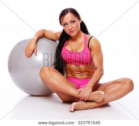 Portrait of joga trainer sitting on the floog with ball