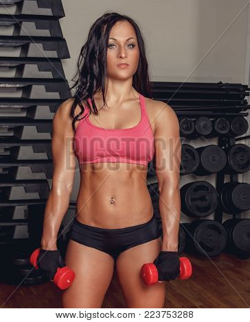 Sexy athletic brunette woman doing exercises with dumbells in a gym.