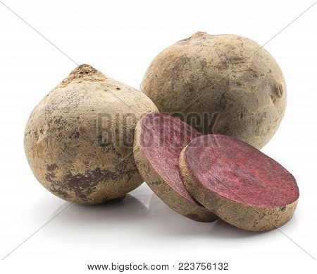 Two beetroot (raw red beet) bulbs and  two slices isolated on white background