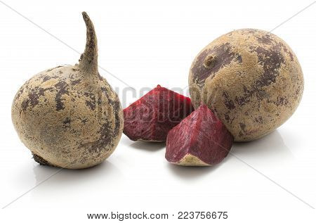 Two beetroot bulbs (raw red beet) and two pieces isolated on white background