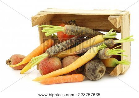assorted root vegetables in a wooden crate on a white background