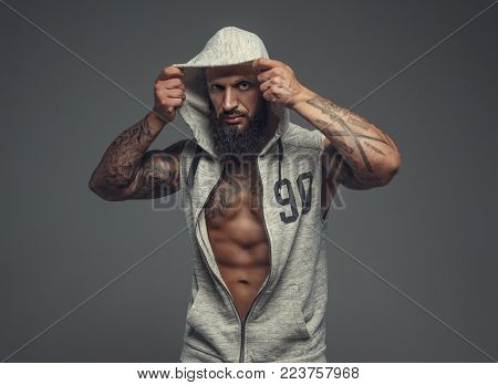 Gangsta tattooed muscular man in a hood. Isolated on grey background.