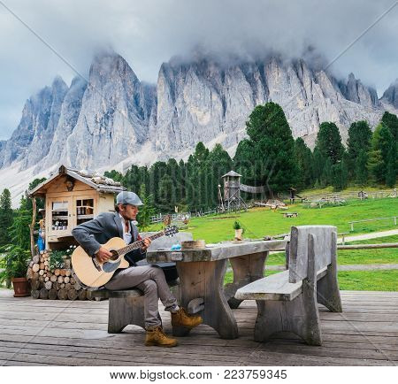 Dolomites, Italy - September 9th, 2017: Young well-dressed man 30-35 playing a guitar with Italian Dolomites rock formation background