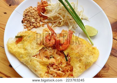 Thai Style Fried Egg Wrapped Stir Fried Noodle or Pad Thai Topped with Shrimps Served on White Plate