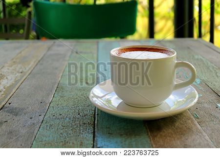 Closed up a Cup of Hot Cappuccino Coffee Served on Rustic Style Wooden Table, Blurred Background