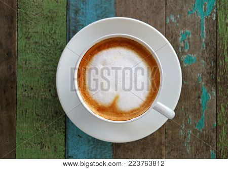 Hot Coffee with Heart Shaped Latte Art in a White Cup on Colored Rustic Style Wooden Table,Top View with Selective Focus