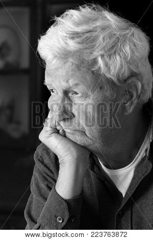 Senior gentleman with serious expression. Depression and loneliness concepts. Visible hearing aid in his ears. Black and white.