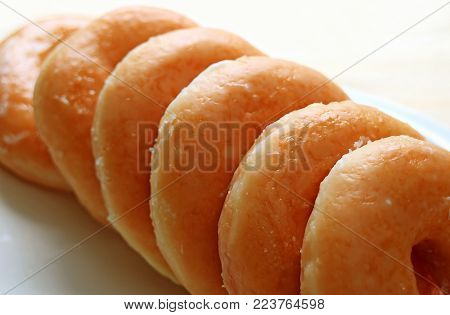 Closed up of Lined up Sugar glazed Donuts with Selective Focus and Blurred Background
