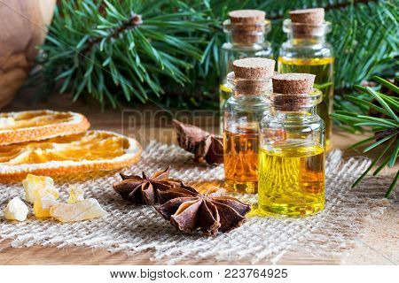 Selection of essential oils with Christmas spices and ingredients: bottles of essential oil, pine branches, frankincense resin, star anise, dried orange slices.