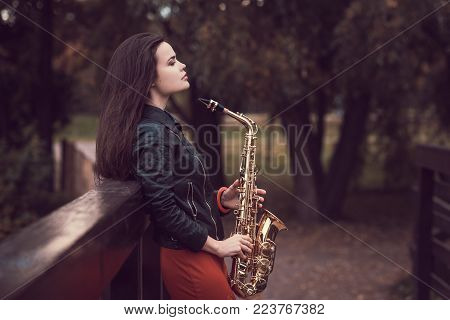 A girl stands with a saxophone in autumn Park on a wooden bridge