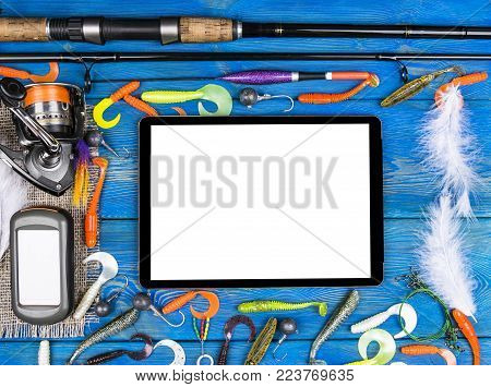 Fishing rod, tackles and fishing baits, reel on wooden board background with tablet computer isolated white screen, empty space for text