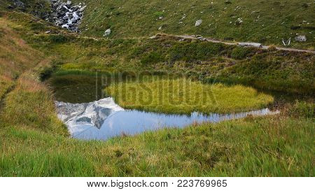 Reflection Of A Snow Covered Mountain In A Small Pond