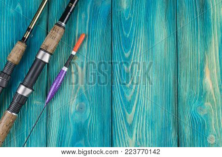 Fishing tackle - fishing rod fishing float and lures on beautiful blue wooden background