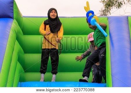 Labuan,Malaysia-Jan 18,2018:Asia kids having fun in inflatable bounce castle at kids outdoor playground toy in Labuan,Malaysia.