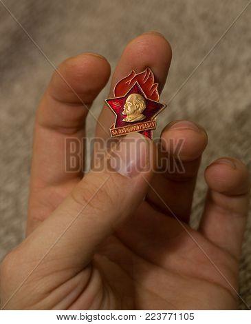 the Communist Soviet pioneer badge in hand