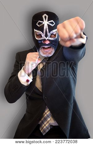 portrait of businessman with wrestler mask and fighting position