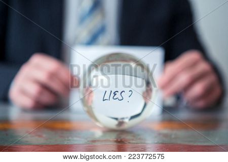 closeup of man holding paper with the word Lies in front of glass ball