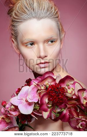 Beautiful girl, isolated on a pink background with varicoloured flowers, emotions, cosmetics