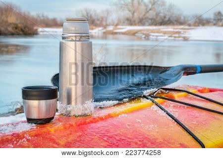 winter kayaking in Colorado - thermos bottle with hot tea on the icy deck of a red whitewater kayak on shore of St Vrain Creek
