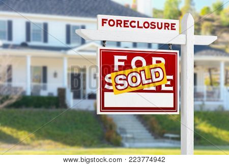 Left Facing Foreclosure Sold For Sale Real Estate Sign in Front of House.