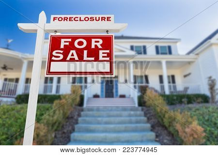 Right Facing Foreclosure For Sale Real Estate Sign in Front of House.