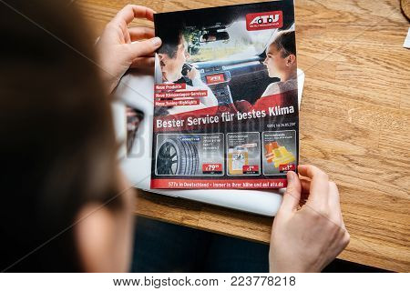 PARIS, FRANCE - APR 26, 2017: Elevated view woman reading A.T.U Auto-Teile-Unger German automotive services advertising leaflet with accessories and car care products such as tires and services