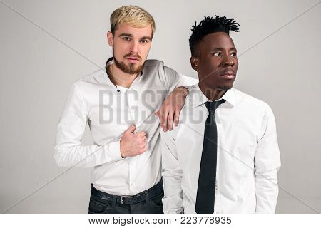Two stylish men posing and having fun on white background. Friends. Two guys in white shirts and dark pants at studio