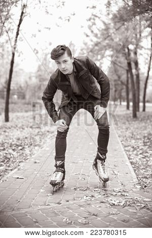 young attractive guy roller skating in the park