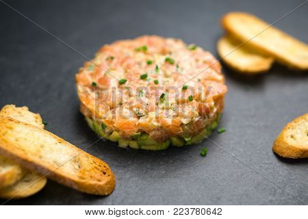 Salmon tartare is made with chopped fresh raw salmon fish, avocado, tartar sauce and crackers or bread. This healthy dish is often served as appetizer in fine dining restaurants.