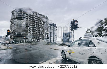 Canberra, Australia - Apr 26, 2017: On Parkes Way and Edinburgh Avenue on a stormy autumn day. Rain distorts image through the car's windshield to reveal a swirling impressionist art effect. Hotel hotel building in front.