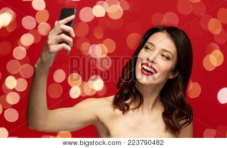 beauty, make up and people concept - happy smiling young woman with red lipstick taking selfie by smartphone over red background with lights